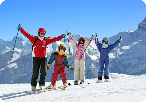 enfants au ski qui posent pour la photo en levant les bras